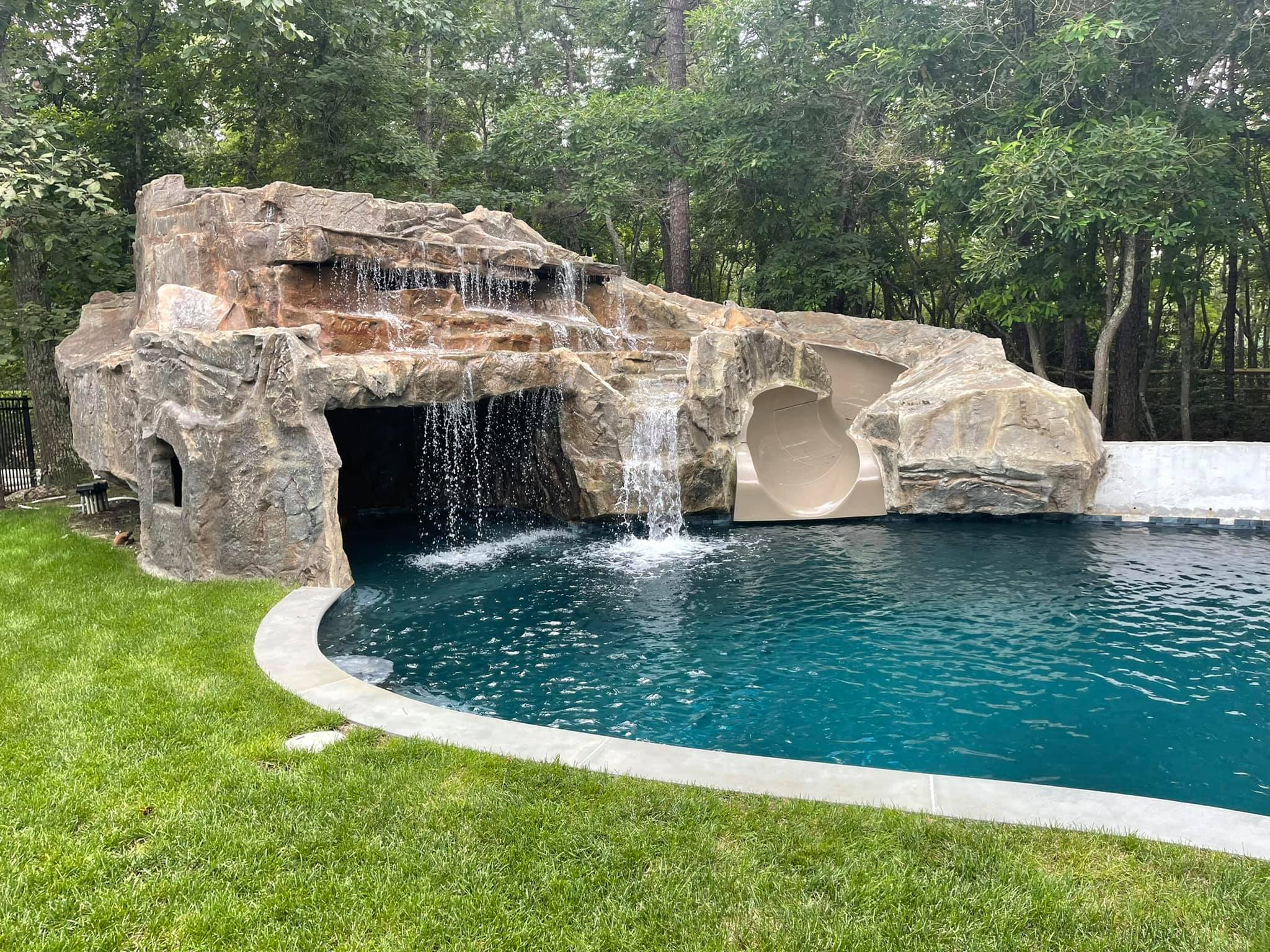 dugybear outdoor living Pool slide with waterfall and cave